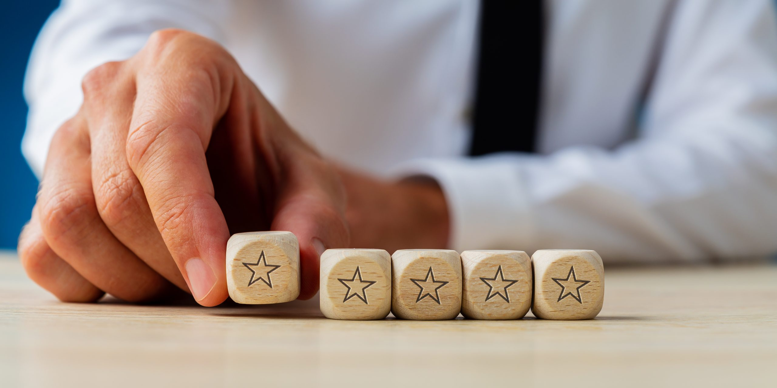 Hand of a businessman placing five wooden dices with star shape on them in a row in a conceptual image.